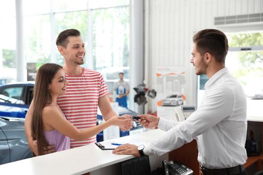 Salesman giving car key to happy couple in salon