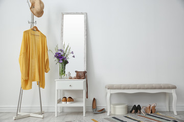 Stylish hallway interior with mirror and rack