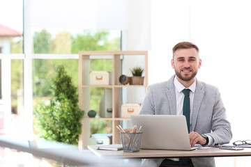 Young businessman using laptop at table in office