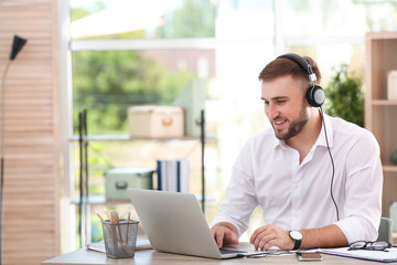 Young businessman using laptop and listening to music at table in office