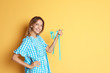 Happy young woman holding fork with measuring tape on color background. Weight loss diet