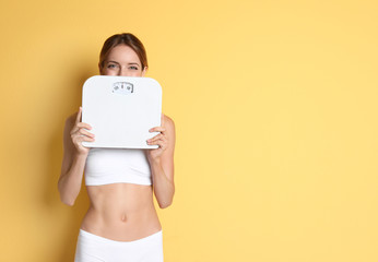 Happy slim woman satisfied with her diet results holding bathroom scales on color background