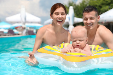 Happy parents with little baby in swimming pool on sunny day, outdoors