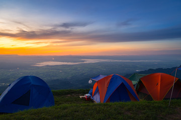 view of tourist tent on green meadow at sunrise. Adventure travel active lifestyle. Camping in the mountains. Tents against the beautiful mountains.