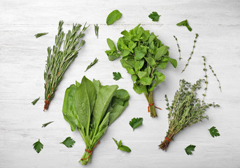 Flat lay composition with fresh green herbs on white wooden background