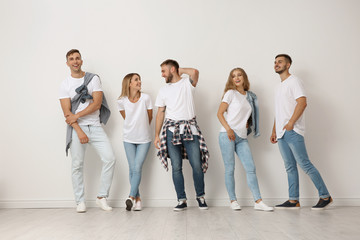 Group of young people in jeans near light wall
