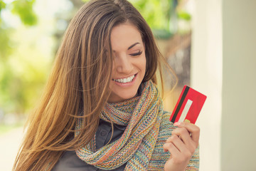 Cheerful excited young woman with credit card standing outdoors