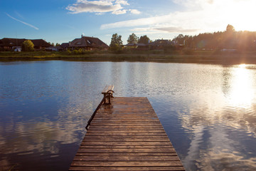 Beautiful wooden pier with clouds and sun reflected on calm and blue water