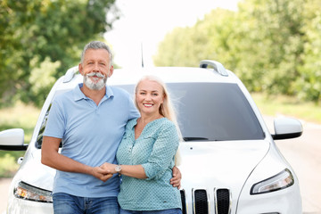 Happy senior couple posing near car outdoors
