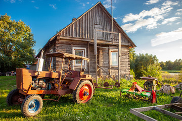 Typical Lithuanian wooden house with old tractor in the countryside on a summer evening