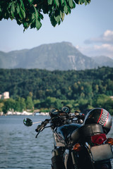 classic style cafe racer motorcycle at sunset time. Bike custom made in vintage. Brutal fun urban lifestyle. pier boats and mountains background