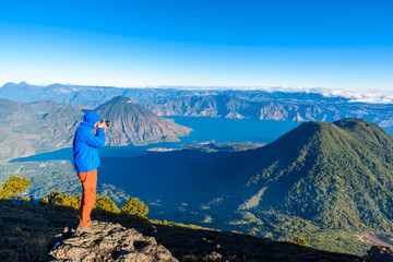 Hiker with panorama view of Lake Atitlan and volcano San Pedro and Toliman early in the morning from peak of volcano Atitlan, Guatemala. Hiking and climbing on Vulcano Atitlan.