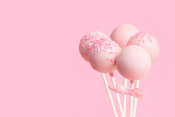 festive glazed cake pops over pink background with copy space, close up