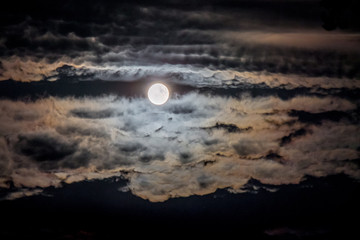 Dark night sky with clouds and moon. The moon illuminates the clouds in the night sky_