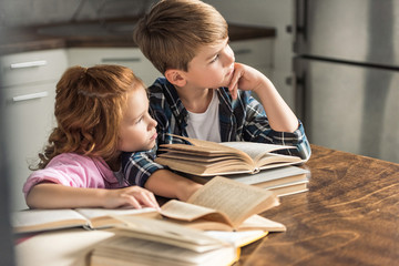 thoughtful brother and sister sitting at table with pile of books and looking away