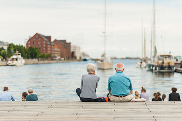 Foto auf AluDibond Schiff Senior couple enjoying a relaxing summer day in the Copenhagen port with boats and yachts in the Old Town. Concept of hygge.