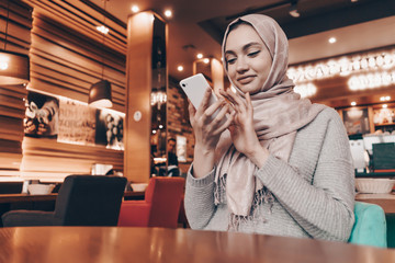 beautiful Arab girl with a headscarf sitting in a cute cafe, writing a message on her smartphone
