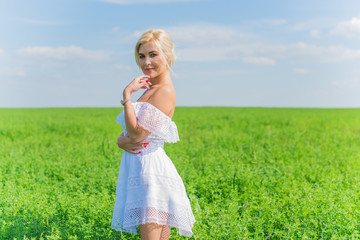 Freedom concept, romantic photo of woman in green field, evening sun, Beauty Romantic Girl in white dress Outdoors. Sunshine