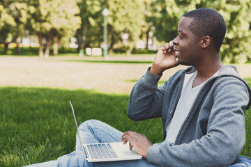 Happy african-american student using laptop in the park