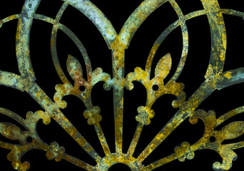 Rusty iron grunge green and yellow lacy metal decoration with fleur-de-lis isolated on black