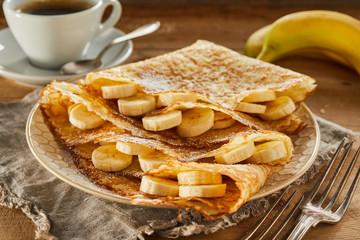 Tasty fresh banana pancakes or wraps with coffee