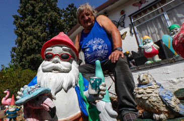 Belgian Gilbert Rassart, an amateur guitarist and former customs agent, sits among some of the hundreds of garden gnomes he started collecting in 2009, in the village of Avennes