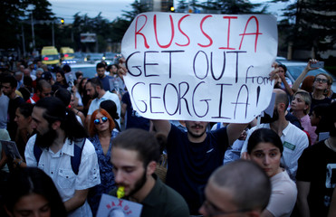 People attend a protest on the 10th anniversary of Georgian Russian war in front of the building of Russian Federation Interests Section of the Embassy of Switzerland in Tbilisi