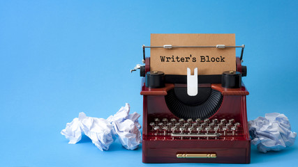 Lack of creative inspiration, writer's block and feeling uninspired concept with an retro typewriter surrounded by crumpled paper balls isolated on minimalist bright blue background with copy space