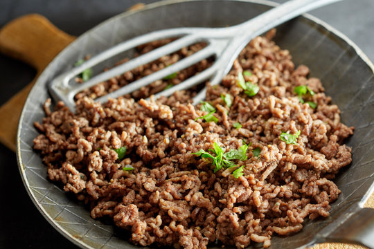 Fried minced meat on pan with green chives