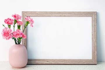 Wooden frame mockup with a pink notched vase with carnations on a desk with the terrazzo pattern
