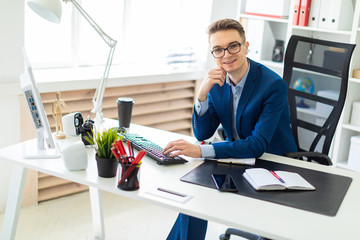 Young man sitting at desk in office and working on computer.