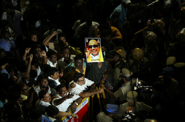 Supporters gather as an ambulance carrying the remains of Indian Tamil leader M. Karunanidhi leaves the hospital in Chennai