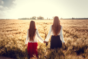Two young women are looking forward tothe sunset. Best friends