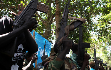 Former child soldiers holds up guns as they participate in a child soldiers' release ceremony, outside Yambio