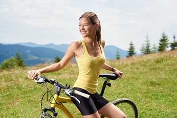 Portrait of attractive happy woman cyclist resting on yellow mountain bicycle, enjoying summer day in the mountains. Outdoor sport activity, lifestyle concept