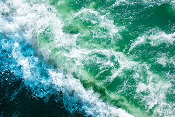 surface of turquoise ocean water with waves, spray and white foam