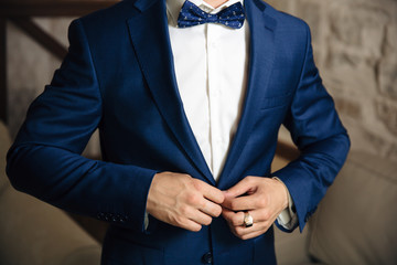 Close-up of a cropped frame of a man buttoning his stylish jacket over a button, wearing a white shirt and a bow tie, a businessman wearing a gold ring on his finger