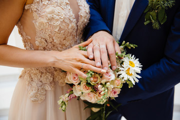 A close-up of a cropped frame of the bride and groom standing side by side and touching their wedding bouquet, showing their wedding rings on the pawls.