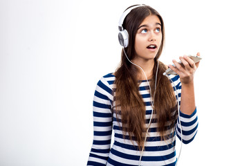 young beautiful girl speaks by mobile phone. Girl with headphones and mobile phone.  student talks to her friend. modern Teenager on a white background