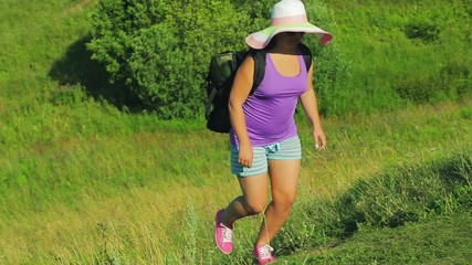 e858cb1c1ec33 0 07 a woman in a straw hat with a backpack rises up the mountain along the  path