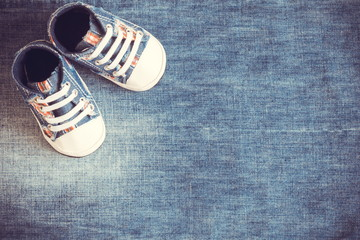 Baby sport shoes on a blue denim background. Flat lay, top view, copy space