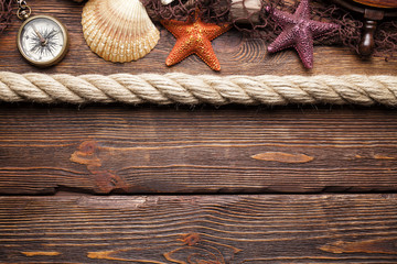Starfish, seashell, fishing net, rope, compass and ship's steering wheel on wooden background