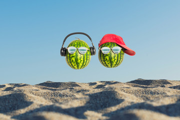 Creative and summer photography of watermelon in the form of a human head with glasses and red cap in the sand on the beach. Concept