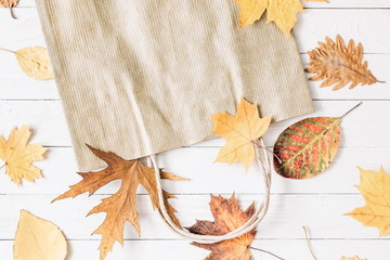 Autumn composition. Paper bag with autumn yellow dried leaves on wooden whute background. Flat lay, top view, copy space