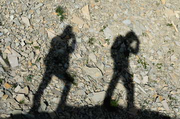 two shadows of photographers on the earth going uphill with up