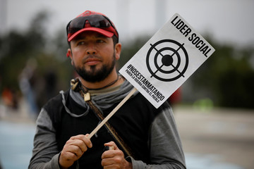 """An opposition supporter carries a banner that reads """"Social leader, we are being killed, stop war against people"""" while people to take part in a rally on the day of the swearing-in of Colombia's new President Ivan Duque in Bogota"""