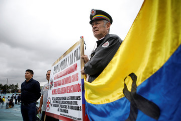 Opposition supporters gather to take part in a rally on the day of the swearing-in of Colombia's new President Ivan Duque in Bogota