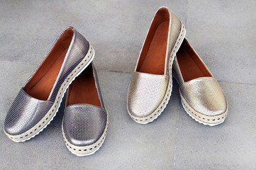 Trendy golden and silver moccasins. Fashionable women's leather shoes.Beauty and fashion concept.