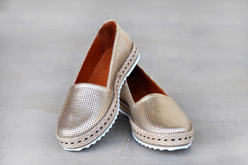 Trendy golden moccasins. Fashionable women's leather shoes.Beauty and fashion concept.