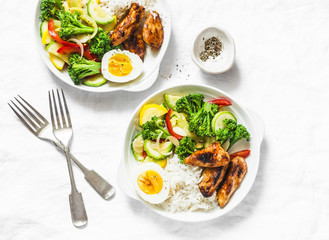Lunch served - stewed vegetables, rice, boiled egg and teriyaki chicken on light background, top view